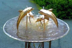 Four copper Dolphins leaping in a fountain
