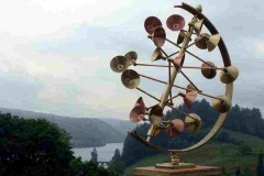 Wind sculpture Global in Brass & Copper with a view of Lake Vyrnwy