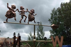 Children playing weathervane made in copper and brass turning on a stainless steel spindle