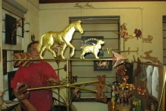 Adding the finishing touches to a weathervane the Horse and hound are finished in gold Leaf